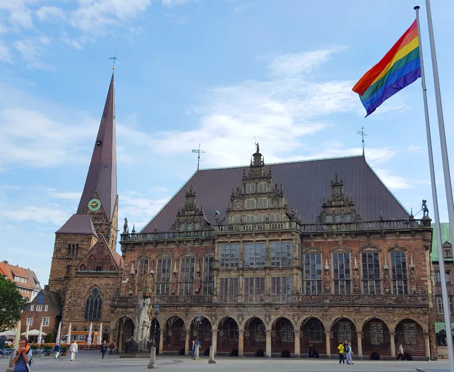 """""""Ehe für Alle"""" - die Regenbogenflagge weht am Bremer Marktplatz. Im historischen Rathaus könnt ihr euch standesamtlich trauen lassen."""