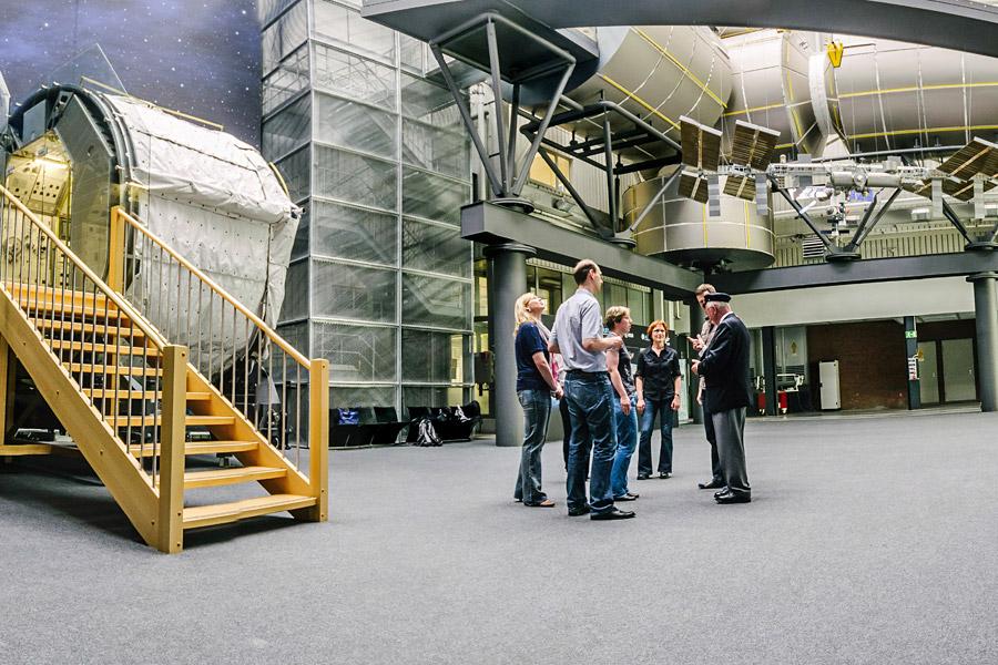 """Hinten rechts: Die ISS als Modell und darüber die begehbaren Module. Vorne links das originale Spacelab, das hier in Bremen Anfang der 1980er Jahre gebaut wurde, dann bis 1998 auf 22 Missionen war und schließlich nach Außerdienststellung wieder an seinen """"Geburtsort"""" zurück kam."""