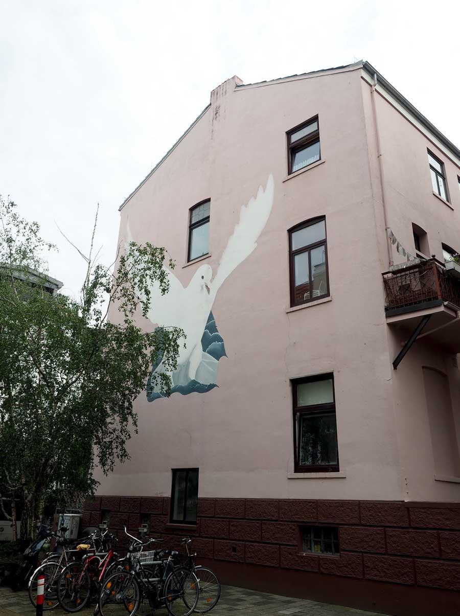 Nicht mehr das Original, wie der Hausbewohner zu erzählen wusste. Die Friedenstaube, die einst mit Zeitung als Kritik zum Nato-Doppelbeschluss vom Künstler Wilfried Siebold abgebildet wurde, wurde im Zuge einer Fassadenrenovierung vereinfacht wieder hergestellt.