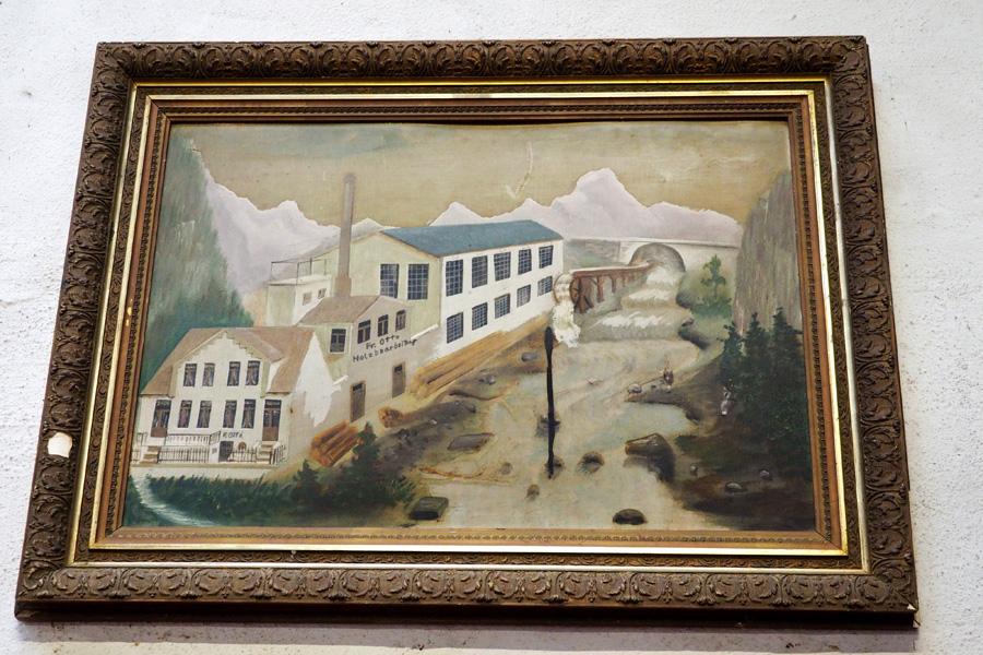 Freie Kunst: Man beachte die Berge im Hintergrund und die Nähe des Flusses. Hier hat der Künstler die Tischlerei kurzerhand an einen anderen Ort versetzt. Das Gebäude an sich entspricht aber in etwa der Realität.